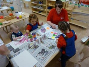 Ava, Charlotte and Cahlan painting with Nursery Staff member Stephanie